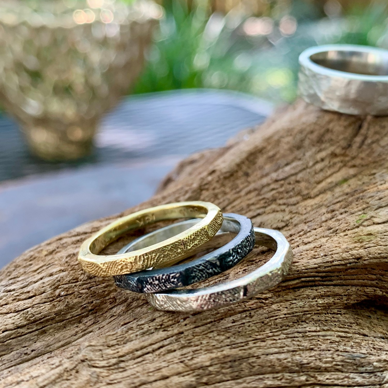 fingerprint stack rings displayed on driftwood